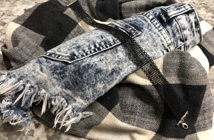 90s outfit elements rest on a bathroom counter, a black choker is draped over rolled-up jean shorts on top of a balled-up black & white flannel button-up shirt